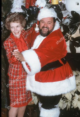 Stock Image of First Lady Nancy Reagan dances with Santa Claus, actor Dom DeLuise during the White House Press Christmas tour of the White House