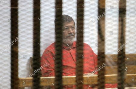 Ousted Egyptian president Mohamed Morsi sits behind bars during his trial