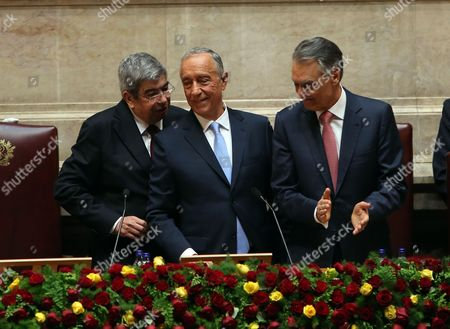New president Marcelo Rebelo de Sousa (C) changes chairs with outgoing president Anibal Cavaco Silva after he swore over the constitution book during his swearing-in ceremony at the Portuguese Parliament in Lisbon