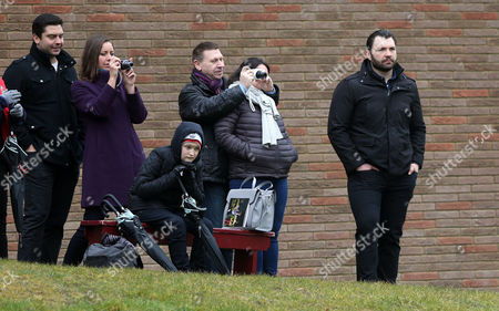 Alex Corbisiero (R) watches training from the sidelines with some invited guests (L)