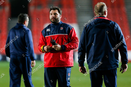 England U20 specialist scrum coach Alex Corbisiero looks on