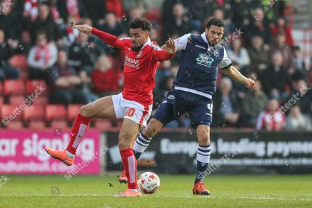 Swindon forward Nicky Ajose & Millwall FC midfielder Carlos Edwards (4) battle for the ball during the Sky Bet League 1 match between Swindon Town and Millwall at the County Ground, Swindon
