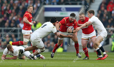 Scott Baldwin of Wales is tackled by Billy Vunipola and Owen Farrell of England.