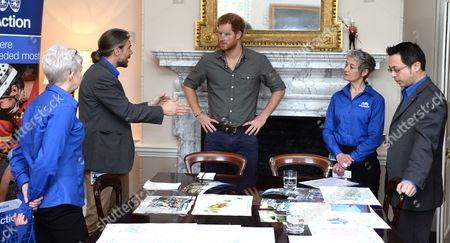 Stock Photo of Prince Harry speaks with MapAction volunteers Kirsty Ferns, Hamish Pritchard, MapAction Chief Executive Liz Hughes and volunteer Wai-Ming Lee during a briefing by MapAction to learn more about the charity's response to the recent Nepal earthquakes, ahead of his tour to the country later this month on March 16, 2016 in London, United Kingdom.