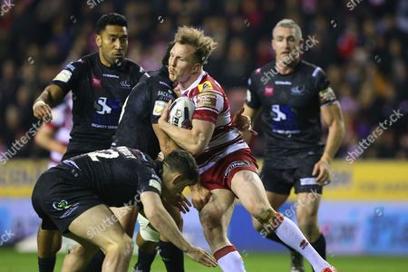 Stock Image of Danny Sarginson is tackled by Eamon O Carroll and Matt Whitley during the First Utility Super League match between Wigan Warriors and Widnes Vikings played at DW Stadium, Wigan on 17th March 2016