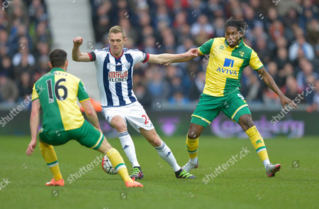 Craig Dawson of West Bromwich Abion runs between Dieumerci Mbokani and Matt Jarvis of Norwich City during the Barclays Premier League match between West Bromwich Albion and Norwich City played at The Hawthorns, West Bromwich on March 19th 2016
