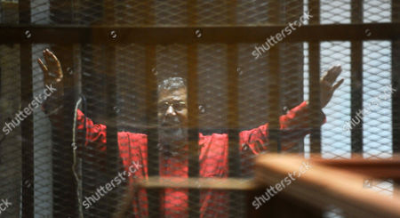 Ousted Egyptian president Mohamed Morsi sits behind bars during his trail as part of the so-called 'Qatar espionage' case, in a court in Cairo