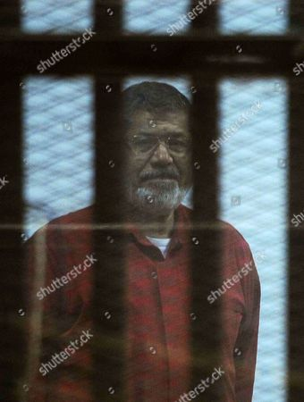 Stock Picture of Ousted Egyptian president Mohamed Morsi sits behind bars during his trail as part of the so-called 'Qatar espionage' case, in a court in Cairo