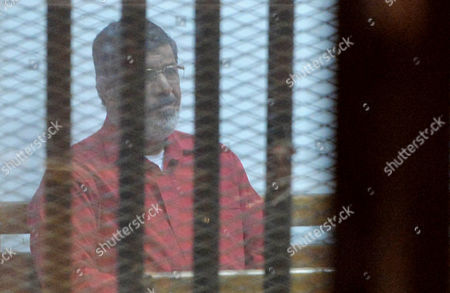 Stock Photo of Ousted Egyptian president Mohamed Morsi sits behind bars during his trail as part of the so-called 'Qatar espionage' case