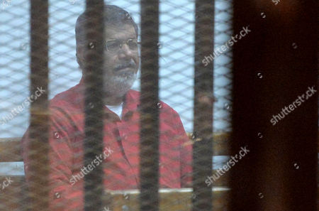 Ousted Egyptian president Mohamed Morsi sits behind bars during his trail as part of the so-called 'Qatar espionage' case
