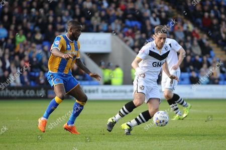 Sam Kelly of Port Vale FC under pressure from Jermaine Grandison of Shrewsbury Town during the Sky Bet League 1 match between Shrewsbury Town and Port Vale at Greenhous Meadow, Shrewsbury