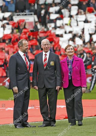 SIR BOBBY AND LADY NORMA WITH CEO EDWARD WOODWARD LOOK UP TO THE NEW SIR BOBBY CHARLTON NAMED SOUTH STAND