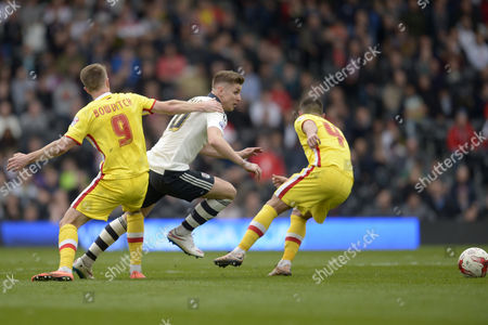 Tom Cairney of Fulham passes Dean Bowditch of MK Dons and Matthew Upson of MK Dons (l) during the Sky Bet Championship match between Fulham and Milton Keynes Dons played at Craven Cottage, London on April 2nd 2016