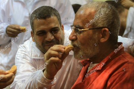 Egyptian Muslim Brotherhood leader Mohammed Badie eats sweets at the defendant's cage as he attends his trial, at a court in the outskirts of Cairo, Egypt
