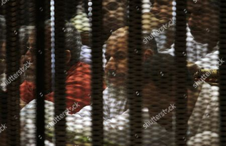 Muslim Brotherhood members sit behind the defendants cage as they attend their trial along with Egyptian Muslim Brotherhood leader Mohammed Badie (unseen), at a court in the outskirts of Cairo, Egypt