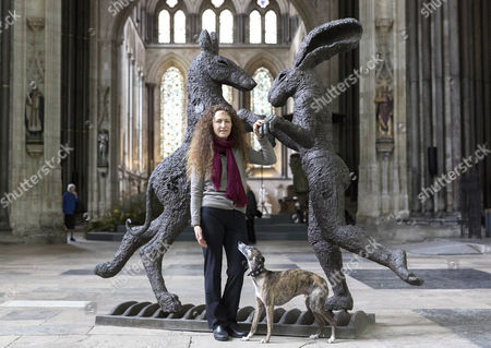 Artist Sophie Ryder poses next to her her bronze Pink Lady Dancing with Brown Dog.