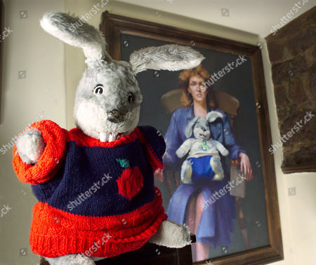 GUS HONEYBUN. IN THE BACKGROUND A LEWIEWICZ PAINTING OF JUDI SPIERS HOLDING