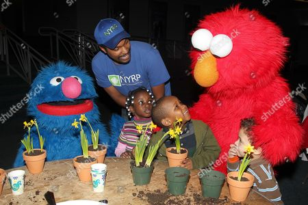 Stock Image of Grover, Omari Washington, Elmo with children from the Garden of Dreams Foundation