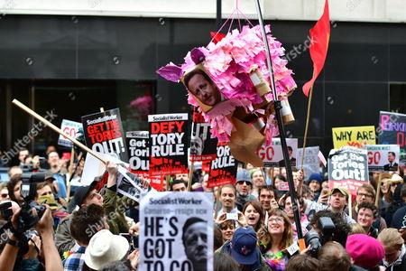 Uncut protestors smash up a pink pig pinata with David Cameron's face on it