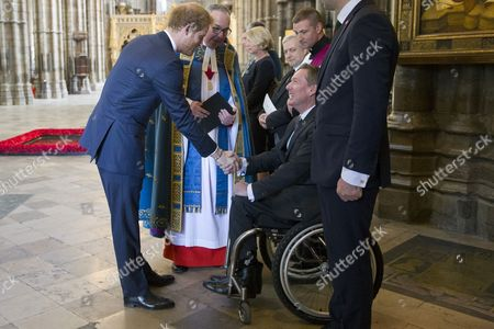 Britain's Prince Harry (L) shakes hands with British journalist Frank Gardner (2R) after a service of commemoration for victims of the 2015 terrorist attacks in Tunisia at Westminster Abbey