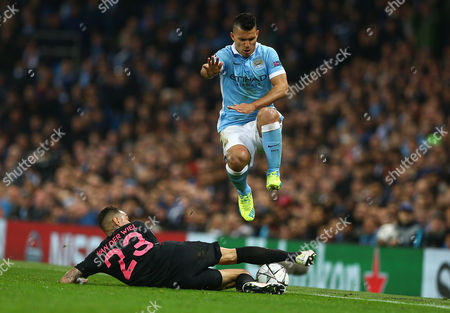 Sergio Aguero of Manchester City hurdles the tackle by Gregory van der Wiel of Paris Saint-Germain during the UEFA Champions League Quarter Final Second Leg match between Manchester City and Paris Saint-Germain played at The Etihad Stadium, Manchester on April 12th 2016