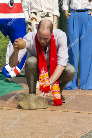 Prince William cracks a coconut during visit to the Mark Shand Foundation