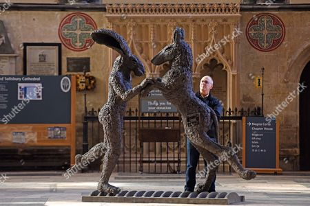 A man looks at sculpture, 'Pink Lady Dancing with Brown Dog'