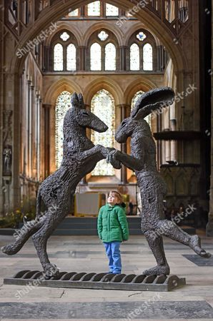 Stock Photo of William Ashton, aged 6, looks at the 'Pink Lady Dancing with Brown Dog' by Sophie Ryder, in the South Transept of the Cathedral