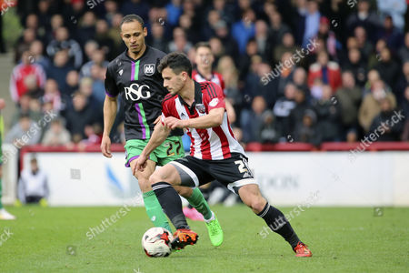 Brentford defender, Maxim Colin (2) screening ball from Bristol City striker, Peter Odemwingie (27) during the Sky Bet Championship match between Brentford and Bristol City at Griffin Park, London