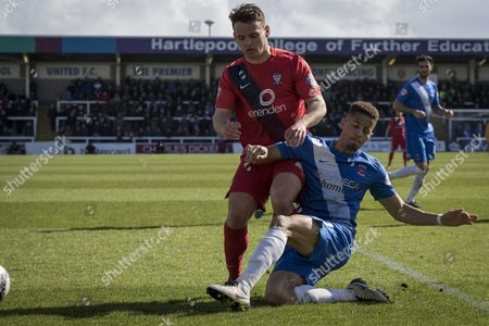 Hartlepool United defender Jake Carroll clears the ball from Reece Thompson of York City FC (22) during  the Sky Bet League 2 match between Hartlepool United and York City at Victoria Park, Hartlepool