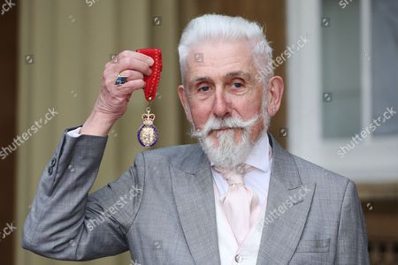 Sir Roy Strong smiles as he holds his Order of the Companions of Honour award