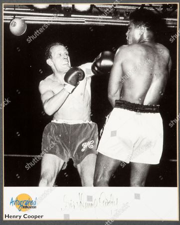 Signed photo of Sir Henry Cooper wearing the gloves during his fight with Muhammad Ali
