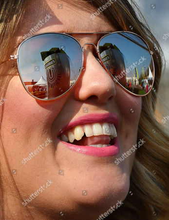 Stock Picture of 9/4/15 Day1 - Grand National Meeting At Aintree Racecourse Merseyside.- Hot Weather Pix - Grand National Sign Reflected In Sunglasses Of Race Goer Sarah Evans From Liverpool.