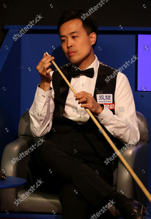 Marco Fu inspects his new cue tip after he had to replace it  when his previous one broke off during the semi final on day 14 of the Betfred World Snooker Championship