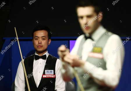 Marco Fu looks on behind Mark Selby during the semi final on day 15 of the Betfred World Snooker Championship 2016 at the Crucible Theatre, Sheffield on 29th April 2016