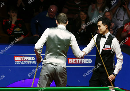 Marco Fu and Mark Selby shake hands after playing in a frame lasting over one hour during the semi final on day 15 of the Betfred World Snooker Championship 2016 at the Crucible Theatre, Sheffield on 29th April 2016