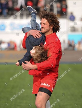 Jacques Burger of Saracens plays with his son as he takes a lap of honour during the Aviva Premiership Rugby match between Saracens and Newcastle Falcons played at Allianz Park, London on May 1st 2016