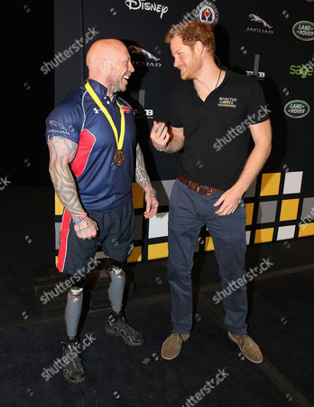 Prince Harry presents Micky Yule with the Powerlift Gold during the Invictus Games Orlando 2016 at ESPN Wide World of Sports on May 9, 2016 in Orlando, Florida.