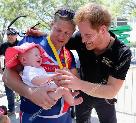 Stock Image of British double gold winner (recumbant cycling) Rob Cromey-Hawke and his daughter Pippa meet Prince Harry at the road cycling event during the Invictus Games Orlando 2016 at ESPN Wide World of Sports on May 9, 2016 in Orlando, Florida.