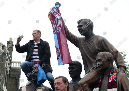 A West Ham United fan sits on the head of Martin Peters, and next to Bobby Moore at the last ever match at Upton Park Stadium / The Boleyn Ground before West Ham's move to the Olympic Stadium during the Barclays Premier League match between West Ham United and Manchester United played at Stamford Bridge, London on 10th May 2016
