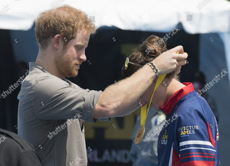 Prince Harry presents USA Invictus Team Member Elizabeth Marks with a Gold Medal at the swimming
