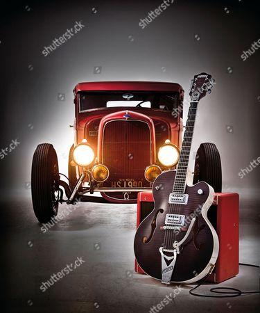 A Gretsch G6120 Brian Setzer Hot Rod Electric Guitar Photographed Alongside A Vintage 1933 Ford Pickup