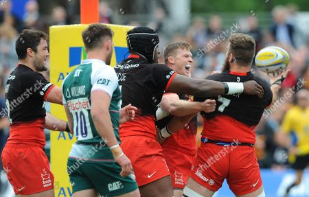 Saracens' Will Fraser (ball in hand)) is congratulated on scoring his try by Chris Ashton (middle) and Maro Itoje (scrum cap)