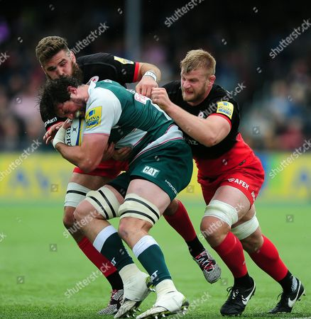 Dom Barrow of Leicester Tigers is double-tackled by Will Fraser and George Kruis of Saracens