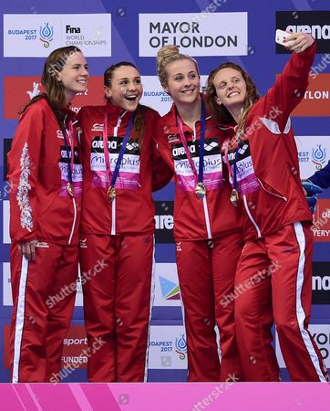 Kathleen Dawson, Chloe Tutton, Siobhan-Marie O'Connor and Francesca Halsall of Great Britain celebrate on the podium after victory in the Women's 4x100m Medley Relay Final.