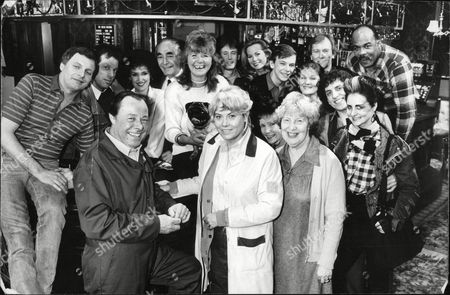 Authoress Jilly Cooper With The Cast Of Eastenders. Back Row L-r: Peter Dean Leslie Grantham Anita Dobson Unknown Jilly Cooper Unknown Shirley Cheriton Adam Woodyatt (the Rest Unknown). Front Row L-r: Bill Treacher Wendy Richard And Anna Wing. Box 631 330091512 A.jpg.
