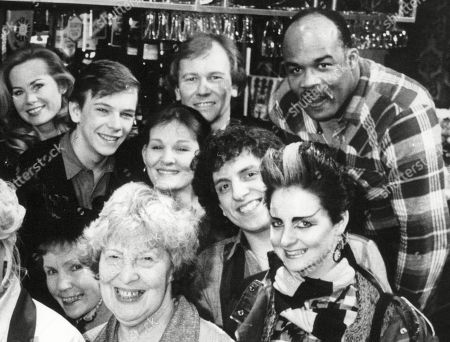 Authoress Jilly Cooper With The Cast Of Eastenders. Back Row L-r: Peter Dean Leslie Grantham Anita Dobson Unknown Jilly Cooper Unknown Shirley Cheriton Douglas fielding (top centre) Adam Woodyatt (the Rest Unknown). Front Row L-r: Bill Treacher Wendy Richard And Anna Wing. Box 631 330091512 A.jpg.