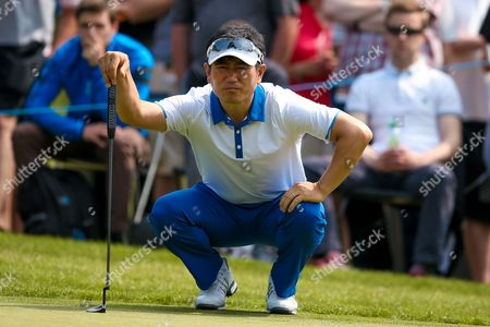 Korean golf professional Y E Yang lines up his putt during the BMW PGA Championship at the Wentworth Club, Virginia Water