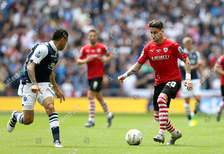 Adam Hammill of Barnsley takes on Carlos Edwards of Millwall