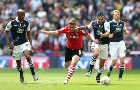 Sam Winnall of Barnsley takes on Carlos Edwards of Millwall
